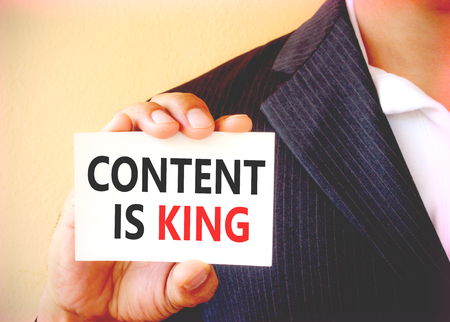 news values: CONTENT IS KING word on the white card shown by a businessman - vintage tone