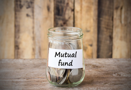 mutual fund: Coins in glass money jar with mutual fund label, financial concept. Vintage wooden background