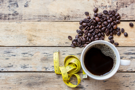 Coffee and yellow measuring tape on wooden table background