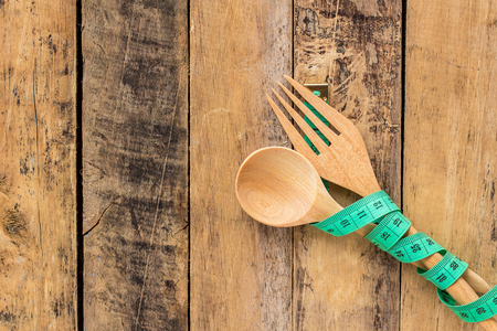 Green measuring tape and wooden spoon and wooden fork on wooden table background Imagens