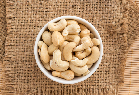 cashews: Close up cashews in the bowl on sackcloth Stock Photo