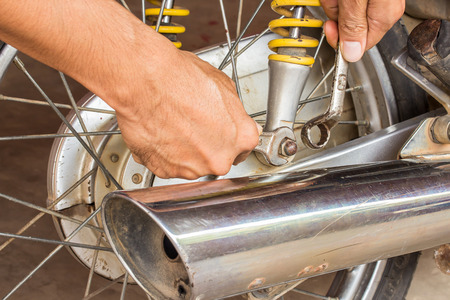 Close up hand holding wrench with mechanic motorcycle repair Stock Photo