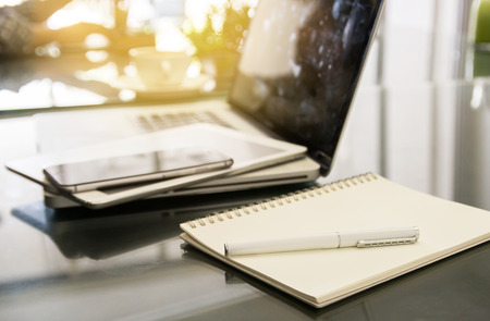 note pad: White pen on notepad with blurred laptop and smartphone background