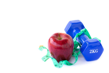 muscle toning: Red apple, dumbbelle and measuring tape on a white background