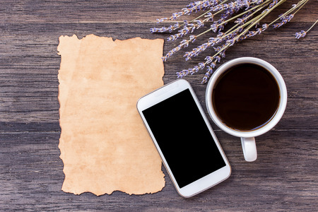 desperado: Old paper, smart phone and cup of coffee with lavender flower on dark wooden table background. top view with copy space
