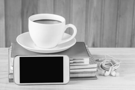 Smart phone and coffee with note book on wooden table background.black and white tone