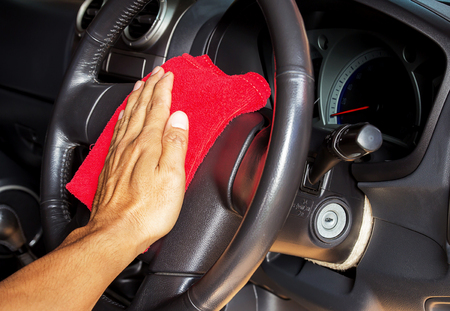 rag wheel: Hand with microfiber cleaning a car steering wheel auto detailing concept