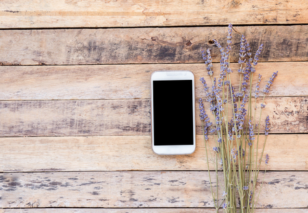 desperado: Smart phone and lavender flower on old wooden table background. top view with copy space