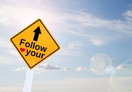 spiritual growth: Text for Follow your hart on yellow road sign with blur blue sky background Stock Photo