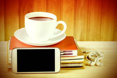 earpiece: Smart phone,coffee cup,and stack of book on wooden table background. Business concept and vintage tone