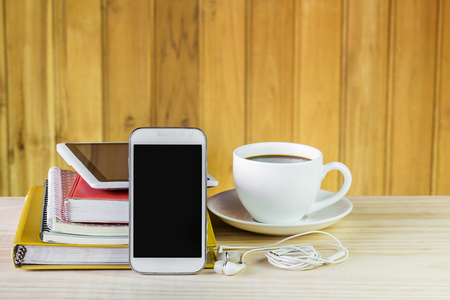 earpiece: Smart phone,coffee cup,and stack of book on wooden table background. Business concept
