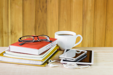 Smart phone,glasses,coffee cup,and stack of book on wooden table background. Business concept