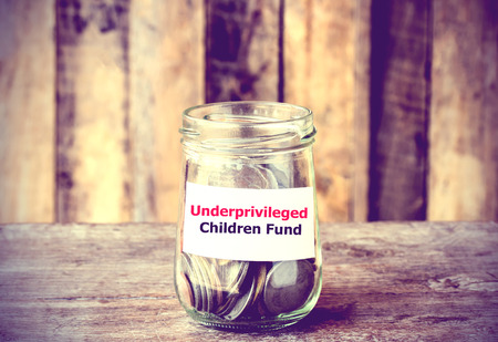 underprivileged: Coins in glass money jar with Underprivileged Children fund label, financial concept. Vintage tone style