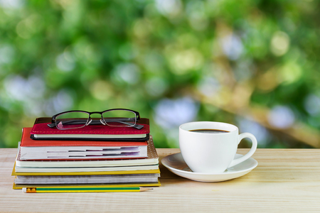 Coffee cup, glasses, and stack of book on wooden table with blur background. Business concept