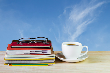 Coffee cup, glasses, and stack of book on wooden table with blur sky background. Business concept