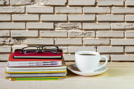 Coffee cup, glasses, and stack of book on wooden table with blur wall background. Business concept