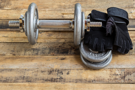 additional training: Top view of dumbbells, extra weights and black gloves on the wooden floor.Sport lifestyle and fitness concept. Stock Photo