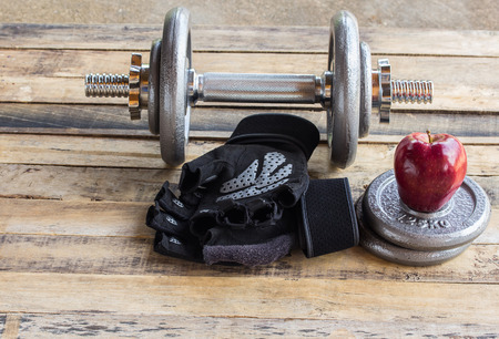 additional training: Red apple and dumbbells, extra weights and black gloves on the wooden floor.Sport lifestyle and fitness concept.