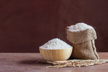Jasmine rice in bowl and sack on old wooden table background with copy space