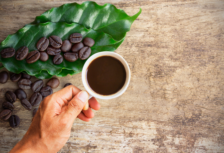 jolt: Business man holding a cup of coffee with coffee beans on wooden table background. copy space