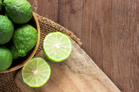 Close up fresh bergamot and bergamot slice in wooden bowl on dark wood table background. bergamot on old wooden brown with copy space. (Bergamot or Kaffir lime)
