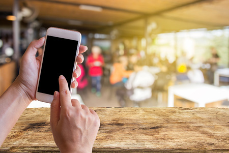 Women hand holding mobile smart phone with coffee shop blur background with copy space. Customer at restaurant blur background with bokeh ,vintage color,food online call shopping
