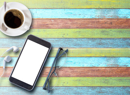 Cup of coffee with smartphone,glasses and earphones on colorful wood table background with copy space for any design. smart phone and coffee cup on wooden top view