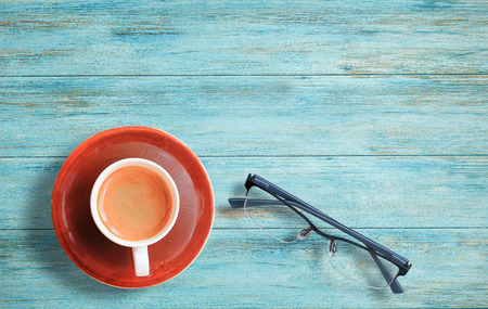 Cup of coffee and glasses on a wood table background. Top view with copy space Stock Photo