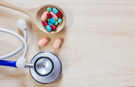 Close up blue stethoscope and pills with tablets on wooden table. Health and medical concept Stock Photo