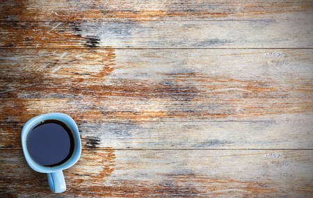 Coffee cup on grunge wooden table. Top view with copy space (selective focus). Office desk table,food and drink concept.