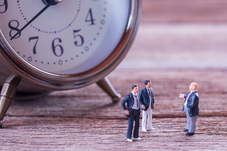 Miniature people: Businessman figures standing on the floor and business negotiations with blurred alarm clock background. money and financial concept. copy space for use as business background Stock Photo