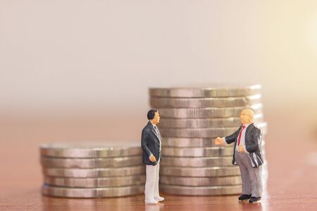 Miniature people : Businessman figures standing on the floor with blurred coin background. money and financial concept. copy space for use as business background or wallpaper. Stockfoto