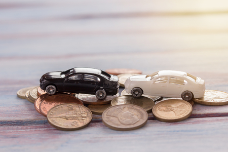 Miniature car- Miniature car crashed car in a city and coin with blurred background. Businessmen are negotiating for auto insurance. Accident and insurance concept.