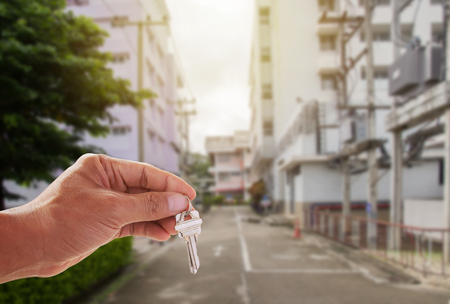Hand holding key with house in the blurred background