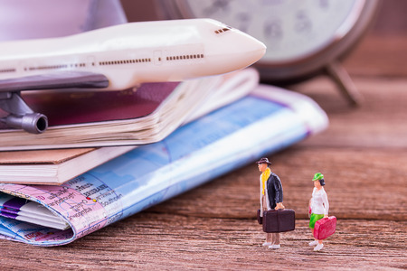 Miniature people traveler standing on the floor and airplane,retro alarm clock,map,notebook on a wooden table. Photo in retro color image style. Top view with copy space.business and travel concept.
