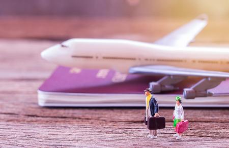 미니어처 사람들 여행자 바닥 및 비행기, 레트로 알람 시계,지도, 나무 테이블에 노트북에 서 서. 레트로 컬러 이미지 스타일의 사진입니다. use.business