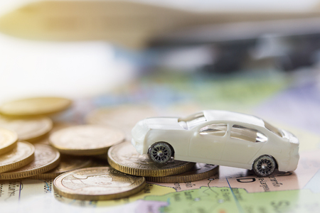 Close up modern of model white toy car park on stack golden coins. Saving, Financial and Installment payment concept. and blurred airplane background. Stock Photo