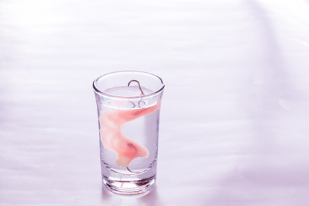 Close up acrylic dentures immersed in a glass of water,table in the bedroom. Bright simple background.