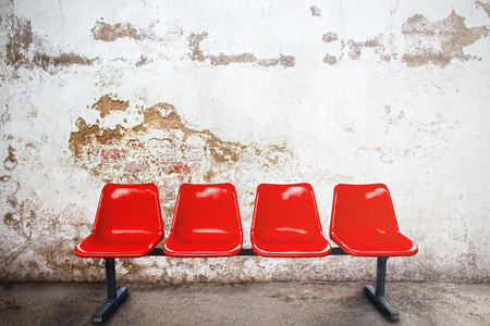 red chair in empty room against a vintage buildings exterior stock