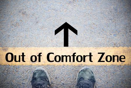 Piedi maschili e vecchie scarpe nere in piedi sul pavimento di cemento o asfalto stradale con linea di demarcazione. Spazio per testo e design e Comfort Zone Concept Archivio Fotografico