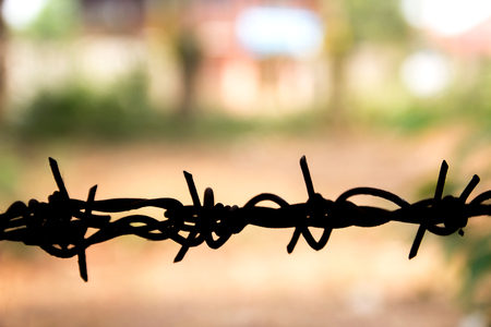 Barbed wire close up with sunshine. Shallow DOF. Space for desing Stock Photo