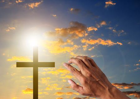 Silhouette cross and people hand in blue sky background symbol for easter sunday, christian and funeral. Archivio Fotografico