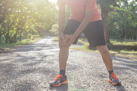 The asian man use hands hold on his knee while running on road in the park. Shot in morning time.sport and workout concept