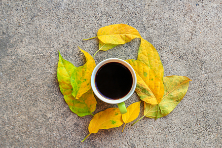 Top view cup of coffee with autumn leaves on cement floor 스톡 콘텐츠