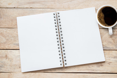 Blank paper notebook and cup of coffee on brown wooden table