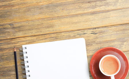 Notepad or notebook with pencil and cup of coffee on brown wood table