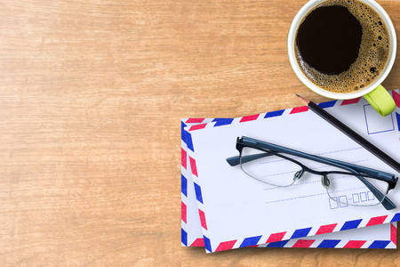 Top view with air mail envelopes,glasses,cup of coffee and black pencil on wood table in office work place