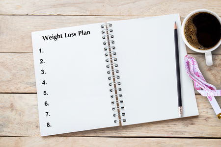 Weight loss program written on book with black listing, planning conceptual.