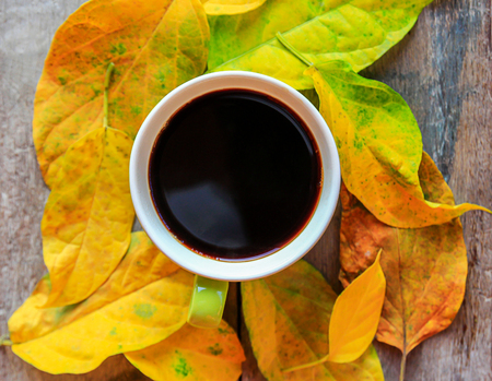 Top view cup of coffee with autumn leaves on old wooden table