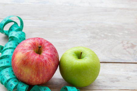 Healthy lifestyle concept with apples. Weight loss or diet concept. Red apple and green measure tape on wood table background with copy space for design